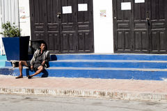Smoke Break. A Lao civilian reclines on the steps of a building as he relaxes for a smoke break Stock Photo