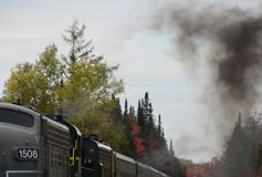 Smoke from burning fuel in the idling locomotive engine. Smoke billows out of smoke stack in top of train on Adirondack Scenic Railroad. NYS; Fall foliage stock images