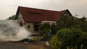 Smoke from Burning Grass in front of Vintage House - Rural Vietnam royalty free stock image