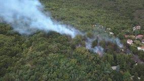 Smoke of bush fire near village houses in Macedonia stock video footage