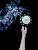 Smoke from candles. Hand holds a extinguished candle from which goes smoke Stock Image