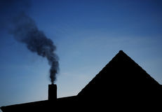 Smoke from chimney. Thick smoke going out of chimney over country house Royalty Free Stock Photo