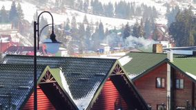 The smoke from the chimney on a background of the. The smoke from the chimney of the restaurant on the background of wooden houses Bukovel ski resort stock footage