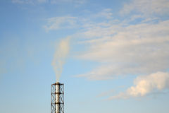 Smoke from a chimney on a blue sky Stock Images