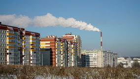 The smoke from the chimney of the plant on the residential area. The urban ecology. The white smoke from the chimney of the plant on the residential area. The stock video footage
