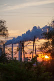 Smoke from chimney power plant station at sunset Royalty Free Stock Photos