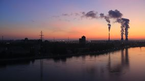 The smoke from the chimneys. In the background of the red dawn in the big city with reflection in river stock video