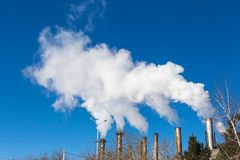 The smoke from the chimneys of the CHP. Pollution of the environment. Environmental disaster. Blue sky Stock Image