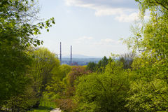 Smoke chimneys far away, viewed from a green park area Royalty Free Stock Photos