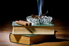 Smoke from cigar with ashtray and two books Stock Photo