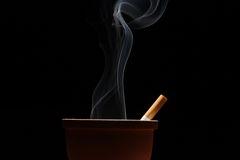 Smoke and cigarette. Smoke of a cigarette in an ashtray on black background Royalty Free Stock Photography
