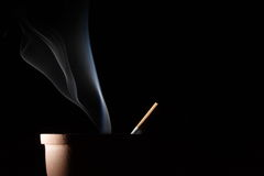 Smoke and cigarette. Smoke of a cigarette in an ashtray on black background Stock Photography