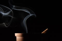 Smoke and cigarette. Smoke of a cigarette in an ashtray on black background Royalty Free Stock Image