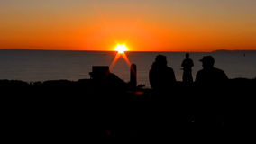 Smoke cigars on a bench overlooking the ocean with a bicyclist taking pictures at sunset. HD 1080. stock video footage