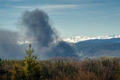 Industrial Burn -  Rising Smoke Cloud. A smoke cloud is rising over the forests of northern British Columbia, Canada, caused by an industrial fire in  the stock photo