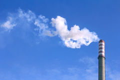 Smoke clouds from a high chimney. White smoke clouds from a high heating plant chimney Stock Images