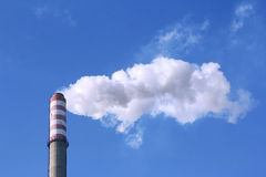 Smoke clouds from a high concrete chimney. White smoke clouds from a high heating plant chimney Royalty Free Stock Photography