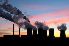 Smoke of coal power plant under sunset sky Stock Images