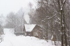Smoke comes from the chimney of a rural house in a snowy forest. Heavy snow in winter day Royalty Free Stock Image
