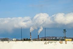 Smoke comes down from the pipes of thermal power plant, horizontally. Smoke comes down from the pipes of thermal power plants, poor ecology, the roofs of the royalty free stock images