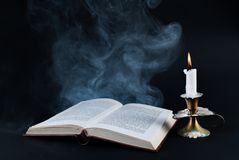 Smoke comes out of old book and candle burning in old candlestick on dark black background Stock Images