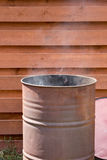 Smoke comes from rusty metal barrel Stock Image