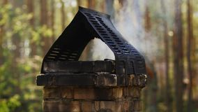 Smoke coming out of the chimney in a forest house