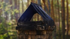 Smoke coming out of the chimney in a forest house stock footage
