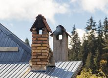 Smoke coming out in the cold from the chimney on the roof of the house. royalty free stock photos