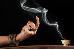 Smoke in command. Woman's hand luring a wisp of smoke Stock Images