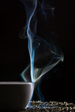 Smoke and cup with grain of tea Royalty Free Stock Photography