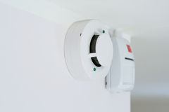 Smoke detector. And alarm mounted on a wall, shallow DOF Royalty Free Stock Image