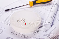 Smoke detector with blueprints and screwdriver Royalty Free Stock Photography