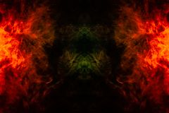 Smoke of different orange and red colors in the form of horror in the shape of the fire on a black isolated background. Soul and. Ghost in mystical symbol stock photos