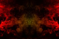 Smoke of different orange and red colors in the form of horror in the shape of the head, face and eye with wings on a black. Isolated background. Soul and ghost royalty free stock images