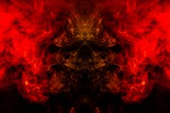 Smoke of different orange and red colors in the form of horror in the shape of the head, face and eye with wings on a black. Isolated background. Soul and ghost royalty free stock photo