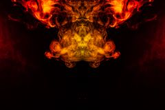 Smoke of different orange and red colors in the form of horror in the shape of the head, face and eye with wings on a black. Isolated background. Soul and ghost stock photos