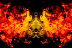 Smoke of different orange and red colors in the form of horror in the shape of the head, face and eye with wings on a black. Isolated background. Soul and ghost royalty free stock photography