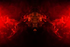Smoke of different orange and red colors in the form of horror in the shape of the head, face and eye with wings on a black. Isolated background. Soul and ghost stock images
