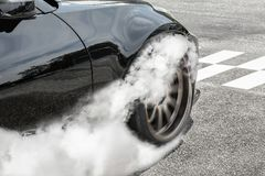 Drag racing car burns  tires at start line. Smoke from Drag racing car burns  tires at start line Royalty Free Stock Images