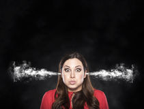 Smoke from the ears of a woman over dark background. Royalty Free Stock Image