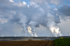 Smoke emission from brown coal fired power plants. Lignite or brown coal fired power plants and wind power plants Stock Photography