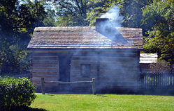 Smoke exits chimney of pioneer cabin. Smoke exits the chimney of an actively-used pioneer cabin at Abraham Lincoln's New Salem State Historical site in Illinois Stock Photography