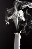 The smoke of an extinguished candle. On black background royalty free stock photography