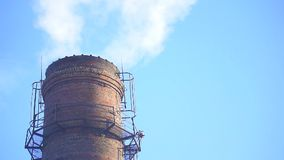 Smoke From the factory chimney. Against the blue sky. Slow motion stock footage