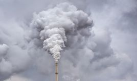 Smoke from factory pipe. Against dark overcast sky stock photography