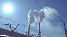 Smoke from factory pipes. Against the blue sky. In the foreground is a barbed wire on concrete fence stock video footage
