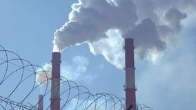 Smoke from factory pipes. Against the blue sky. In the foreground is a barbed wire stock footage