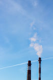Smoke from factory pipes, industrial emissions in blue sky as ecology problem. Royalty Free Stock Photos