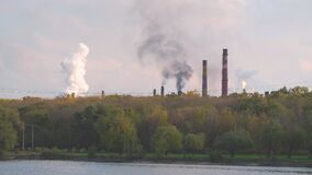 Smoke of factory pipes near a forest and river .